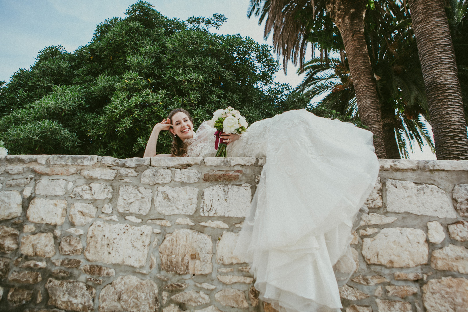 Photo of bride relaxing on a stone wall
