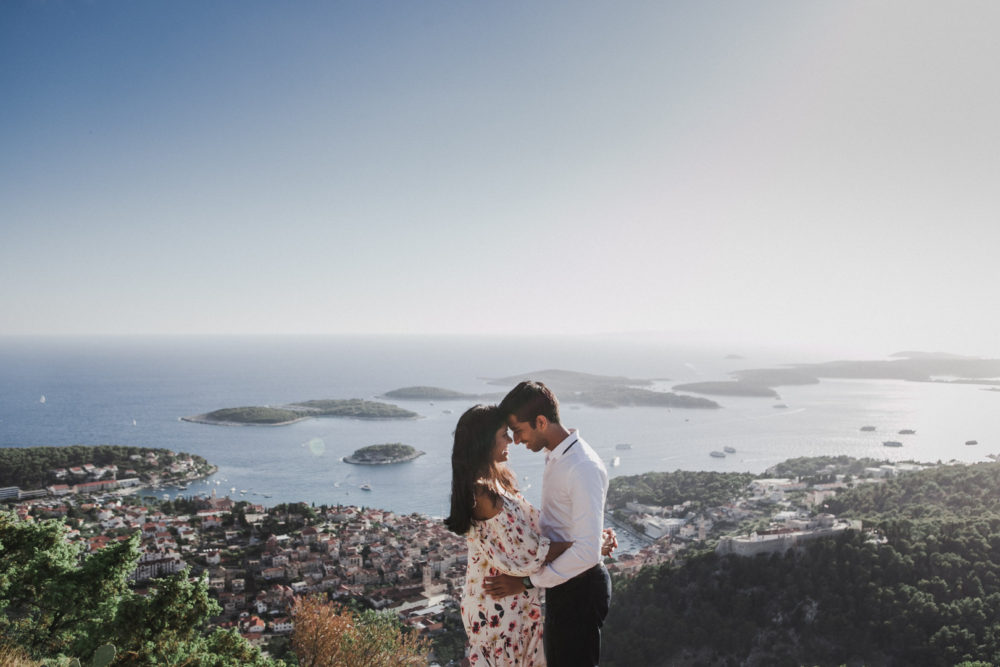 Engaged couple standing on hilltop with view of Pakleni Islands